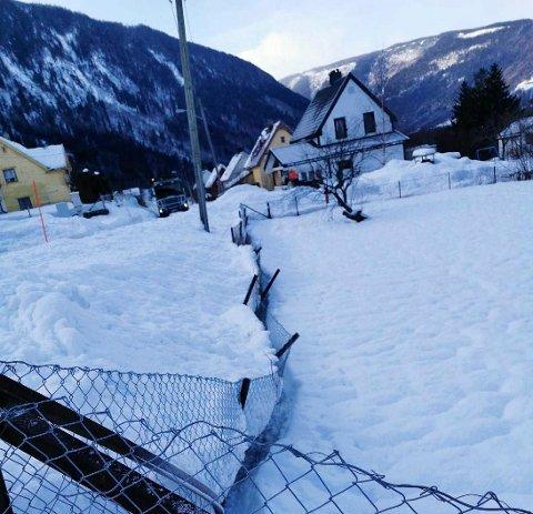 BRØYTING: En huseier i Rollagvegen har sendt Tinn kommune dette bildet av sitt nedpressa gjerde. Nå lover kommunen å se på saken. (fotovedlegg til brevet)