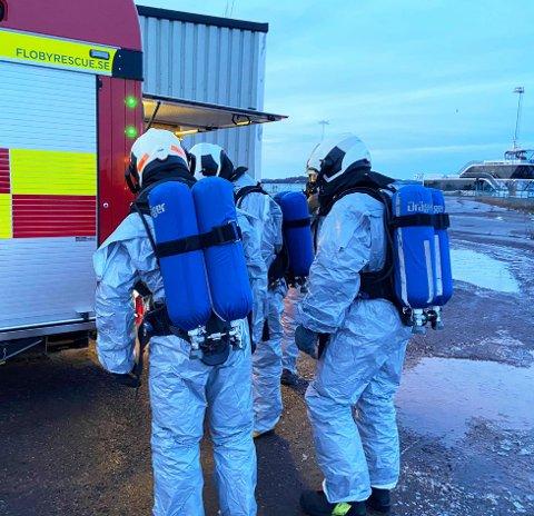 VALLØ STENGT: Brannmannskaper med oksygenflasker og - masker holder oppsyn med havaristen, som ligger fortøyd ved kaien på Vallø.