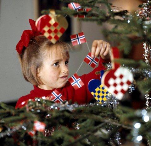 TRADISJONSPYNT: I 1970 var det hjemmeflettede kurver og norske flagg som gjaldt da denne jenta pyntet treet. I dag velger flere en mer moderne stil på juletreet. (Foto: Erik Thorberg / NTB)  FOTO: Thorberg, Erik /