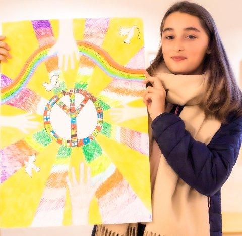Enkela Aliu (12) fra Brønnerud skole med sin tegning hvor bildet viser fire hender som strekker seg mot fred. Hendene har ulike farger og viser at hele verden er med. Hvis alle bidrar så vil det bli fred. Bildet er fint utført og har god fargesammensetning, skriver juryen i sin bedømmelse.