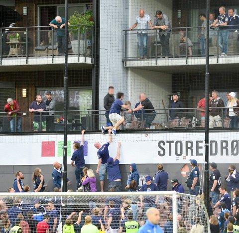 KLATRING: Her klatrer en SIF-supporter oppover Stadionkvartalet i Mjøndalen under lokalderbyet i 2017.