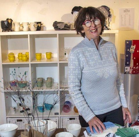 Astrid Tveiten i brukskunstutsalget i Mjøsvågen. Strikkeplaggene er laget på Norlender-fabrikken hun selv styrer.