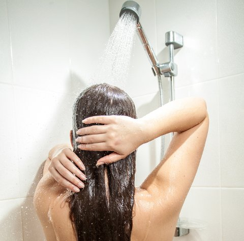Photo from back of sexy woman with long hair having shower