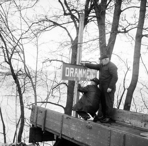 BLE DRAMMEN: Tidlig morgen 1. nyttårsdag i 1964. På Tørkop på Svelvikveien er arbeidere i ferd med å sette opp Drammenssskiltet i den nye store kommunen.