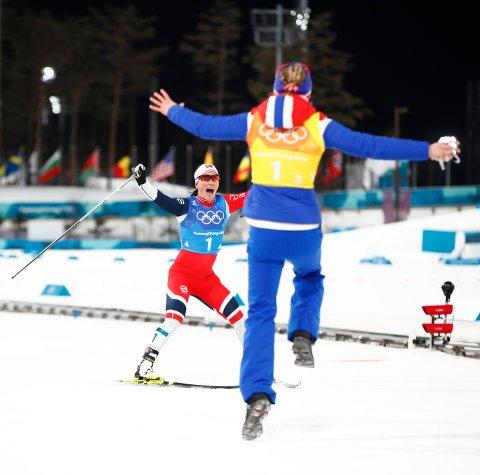 Ragnhild Haga hopper av glede og løper mot Marit Bjørgen etter OL-stafetten lørdag. Foto: Terje Pedersen / NTB scanpix