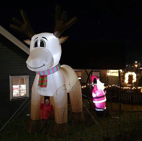 MEGA-RUDOLF: En gedigen oppblåsbar figur prydet hagen til Aina Vindstad Ilebrekke (mellom beina til Rudolf) og husbonden Magnus. Den er hele fem meter høy, fire meter lang og 2,3 meter mellom gevirtuppene. FOTO: Privat