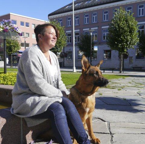 Et hundeliv: Maryann Arnesen jobber i parkvesenet. Her sitter hun og hunden Vito og nyter høstsola i Byparken. Hjemme har hun to schæfere til, og hun er aktiv i hundemiljøet, både her og på Kongsberg.Foto: Jørund Løbach Jørgensen