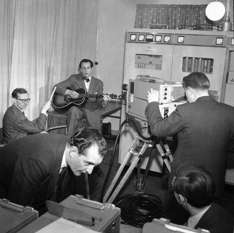 Først i TV-studio:  Norsk Rikskringkasting starter prøvesendinger for fjernsyn i 1954. Her fra fjernsynets første prøvesending. Kringkastingens teatersjef Jens Gunderssen spiller gitar i den første prøvesendingen. Kamerafolk var fra Pye Ltd. England.