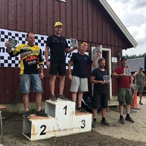 OVERRASKELSEN: Mikkel W. Mikkelsen øvert på seierspallen i endurodebutan i Skien lørdag. André Wolad Larsen (t.v.) ble nummer to og Pål Anders Ullevålster ble nummer tre. FOTO: PRIVAT