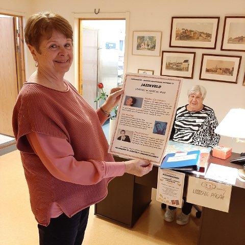 Ellen Scott Garmann er frivillig ved seniorsenteret. Her viser hun frem en plakat hun har laget for jazzkveld arrangementet i mars. I bakgrunnen sitter Annie Stavseth, som også er frivillig på senteret.