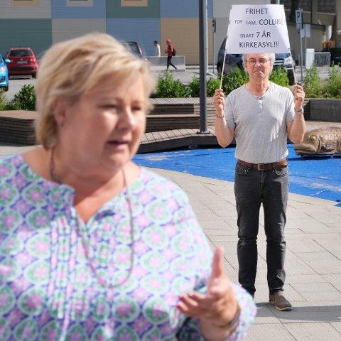 BAK RYGGEN: Odd Fredriksen framførte en stille protest mens statsminister Erna Solberg snakket til sine lokale partivenner på Finnsnes.
