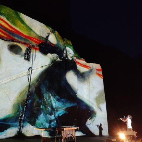 PÅ STEINVEGGEN: Malerier av Vebjørn Sand ble projisert på steinveggene i bruddet under lørdagens spektakulære konsert der.