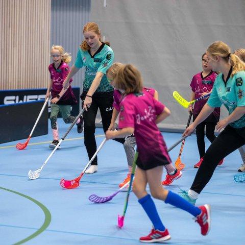 TOPP TRENERE: Førsteårs elitespillere Caroline Hicks Johnsen og Josefine Hermansen spiller innebandy med 4 klassegruppen. Å spille sammen med barna er viktig for å lære de bevegelsesmønster og jobbe med spilleforståelse.