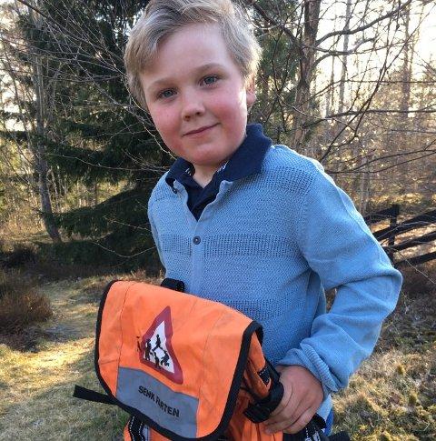 FORNØYD: Nå får Oskar (6) snart sin egen oransje skolesekk. Her låner han sekken som storebror Markus (10) fikk da han begynte på skolen.