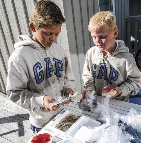 Teller penger: Philip (til venstre) og Christian er nøye på regnskapet og teller penger hver dag.