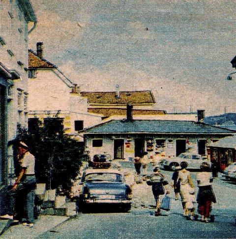 Jens Lauersøns plass i 1964: Dette bildet er litt spesielt. Selv om det er et litt dårlig fargefoto, viser det en spesiell hendelse. Den tidligere Kringsjågården rives. Gården gikk så langt ut i gata som dit den blå bilen er parkert. På den tiden, tidlig på 1960-tallet parkerte folk rundt om hele i hele sentrum, omtrent som de ville. I bygningen midt imot, som tilhører Jens lauersøns legat var det tre virksomheter. Til venstre hadde Tellefsen skomakerverksted. I midten var det en kiosk og til høyre, mot Bybrua var turistkontoret.