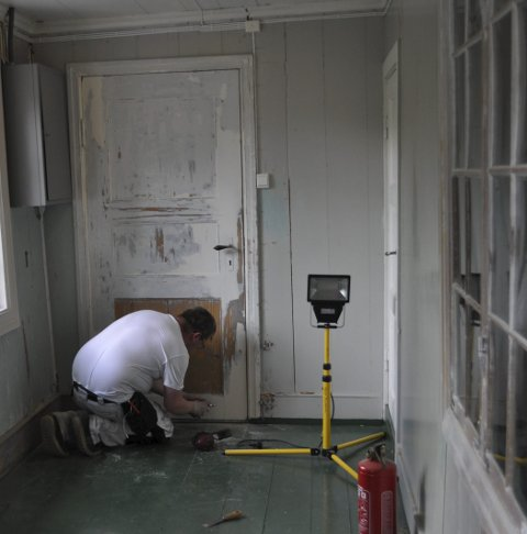 Pusser opp: En håndverker skraper gammel maling av dørene i andre etasje i presteboligen. Foto: Trude G. Dale