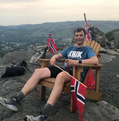 """FERDIG: Georg Feed (42) etter 73 turer opp Helgelandsfjellet i Førre. Her får han seg en velfortjent hvil på toppen av """"Mount Everest"""", omkranset av norske flagg."""