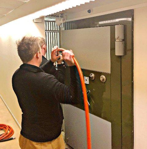 INNESTENGT: Her jobber brannmannskapene på med trykkluft for å få åpnet døra til bankhvelvet, der en person satt innelåst.
