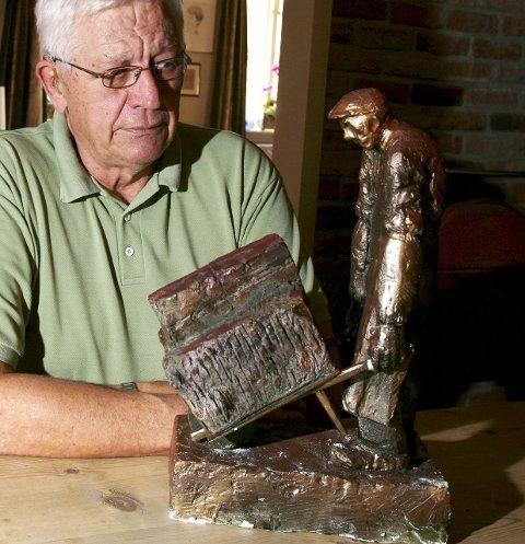 Initiativtaker Odd Løkkevik med en modell av skulpturen av teglverksarbeideren som skal få plass på Sorgenfri. Kunstneren er Svein-Tore Kleppan.