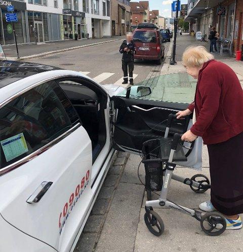 FÅR BOT: Her får taxisjåfør Tron Sjølli 900 kroner i bot av parkeringsvakta mens han hjelper 80 år gamle Ellen Myrvold ut av butikken. Nå reagerer han sterkt på det han mener viser mangel på skjønn. Foto: Privat