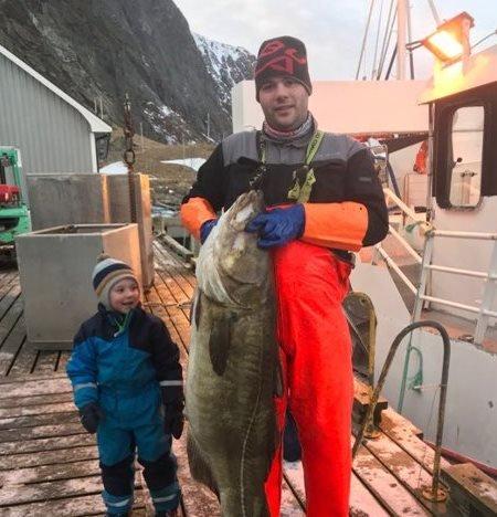 """2018:  Tor Petter Kristiansen med årets første kaffetorsk I 2018. Den veide 32,5 kilo og ble tatt av """"Eggumsværing"""". Noah ser storøyd på den store fisken."""
