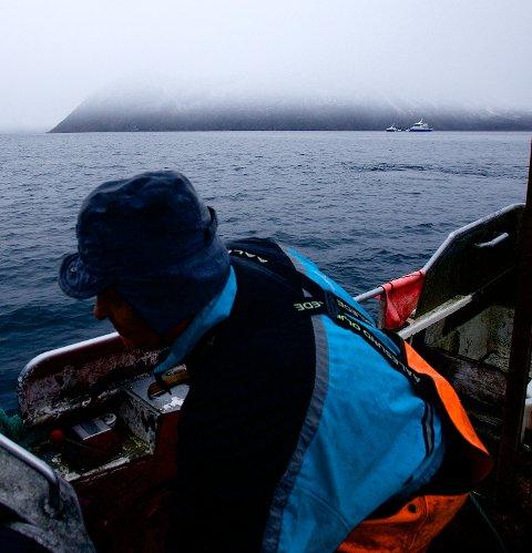En søkklastet brønnbåt passerer mens fisker Jarle Olsen trekker garna ved Ravelsnes. Nå vil oppdrettsindustrien legge beslag på dette fiskefeltet ved Spildra i Kvænangen. Der garnblåsene nå står, kan det om kort tid ligge oppdrettsmerder. – Da er det slutt for oss, sier Olsen. Foto: Ola Solvang