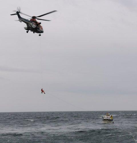 REDNINGSHELIKOPTERET: Her blir redningsmannen om bord i helikopteret frå Florø heisa ned til havaristen. Bilda er henta frå Redningsselskapet på Twitter.