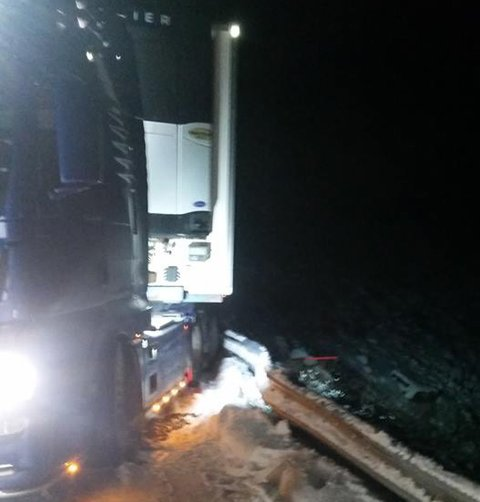 HANG PÅ AUTOVERNET: Semitraileren hang på autovernet som var i ferd med å gi etter. Sjåføren hoppet ut i fart da kjøretøyet begynte å skli bakover.