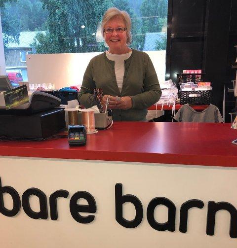 BAK DISKEN:  Kari Bjørg Wiken Hoftuft har solgt barneklær siden 1979. Butikken runda 50 år 7. juli, men nå er det snart slutt.