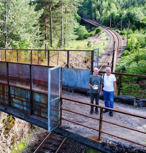 BEFARING: Vidar Askland e her sammen med Roy Olsen på befaring og testflyging med drona ved Bærugbrua. Roy er kamerat,og kjentmann langs linja, og hjalp til med å finne de rette stedene å stå for filmingen.