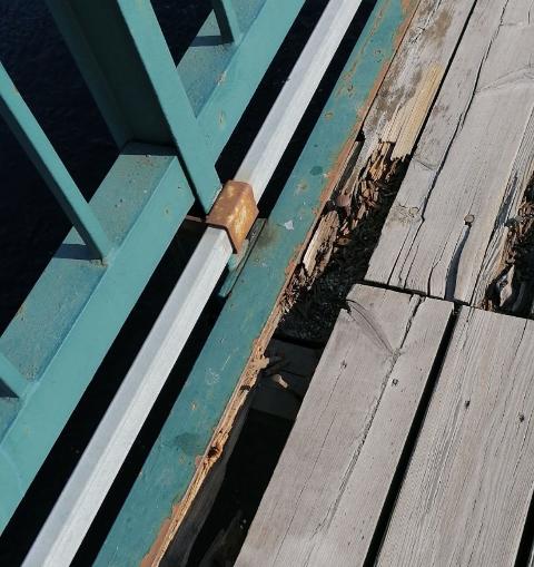 Flere av plankene på gamlebrua er løse og råtne.