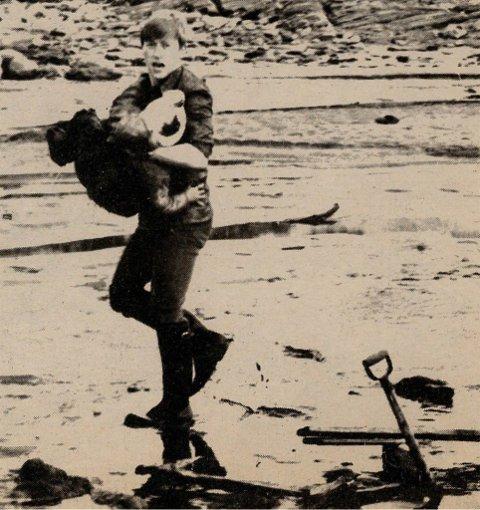 REDNING: Oddvar Jenssen redder opp en av ungene fra Leira i havnebassenget i Mehamn.