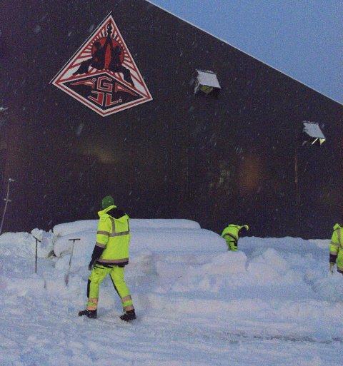 KAldhall: Det er kaldt både inne i og utenfor hallen på Hauknes. Arbeiderne fra Unisport graver her fram de småfrosne rullene med kunstgress som skal legges. Foto: Vegard Anders Skorpen