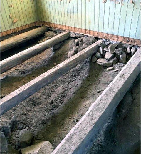 Bildet viser hvordan terrenget som heller inn mot stua på Kvernstua på nordsiden fortsetter inn under konstruksjonen og slik leder vann inn under gulvet. På denne måten forårsaker vannet skade både på gulv og vegger.