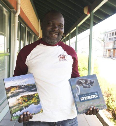Vil sørge for en framtid: Kisitu Nelson selger bøker til inntekt for et utdanningsprosjekt i Uganda. Her med to av de nye bøkene han tilbyr.Foto: Lena Malnes