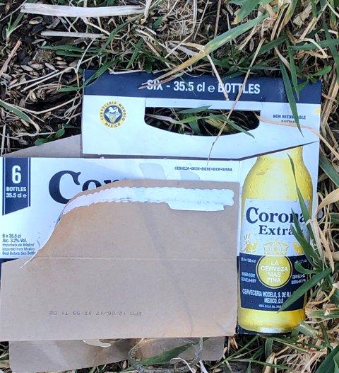 CORONA-AVFALL: Denne sekspakningen med Corona er blant avfallet som er kastet i ei parkeringslomme langs fylkesvei 114.