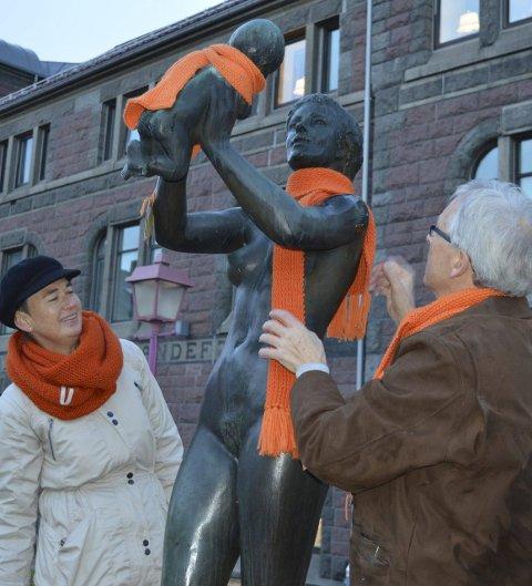 «Mor og barn» fikk skjerf: Melle Aakenes og Arne Sandberg kler opp statuen i Byparken tidlig tirsdag morgen. Foto: Jan Roaldset