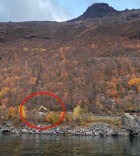 I RASOMRÅDET: Gravemaskinen er i gang med arbeidet på E6. I fjellsida ser man hvordan steinen har rullet ned før den traff E6. Foto: Vegard Molberg