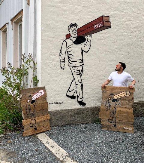Rune Francisco Fauske med sine tre nyeste kunstverk: Gatekunst av plankebæreren, samt to på treplanker som kan henges på veggen.