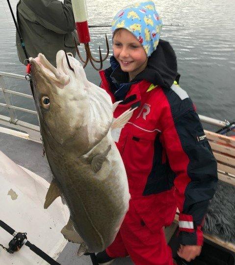 RUGG: Sebastian Lien (10) fra Nes elsker å fiske, og det var et stort høydepunkt da denne digre torsken ble dratt opp fra havet på ferie i Tromsø.