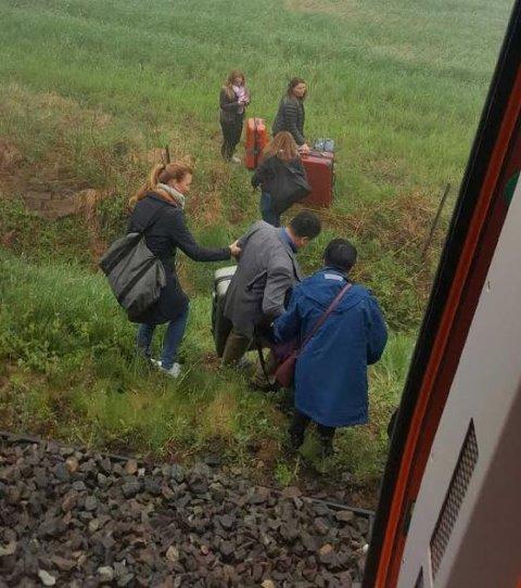 HELT PÅ JORDET: Passasjerene hjalp hverandre ut av toget.