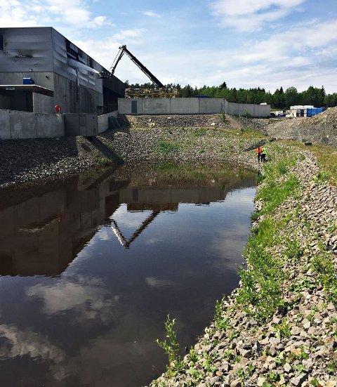 STOR DAM: Her renner slukkevannet. Nå skal mye av vannet suges opp og fraktes vekk, for å senke risikoen for ukontrollert avrenning.