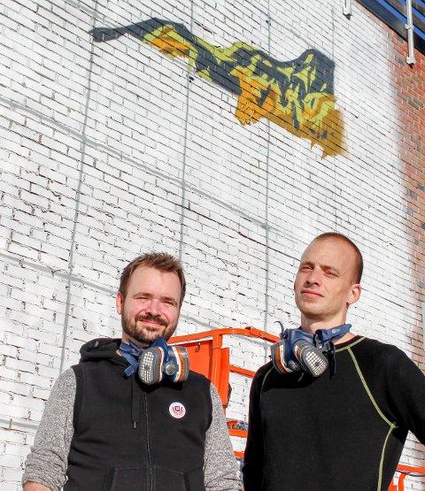 Mosjøen: F.v. Tor Erik Bugge og Marius Alexander har sammen 50 års erfaring med utsmykningsarbeid. Nå er de i gang med å male en mosjøinspirert vegg.