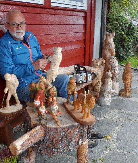 Kjell Musland med eit knippe av treskulpturane sine. (Pressefoto).