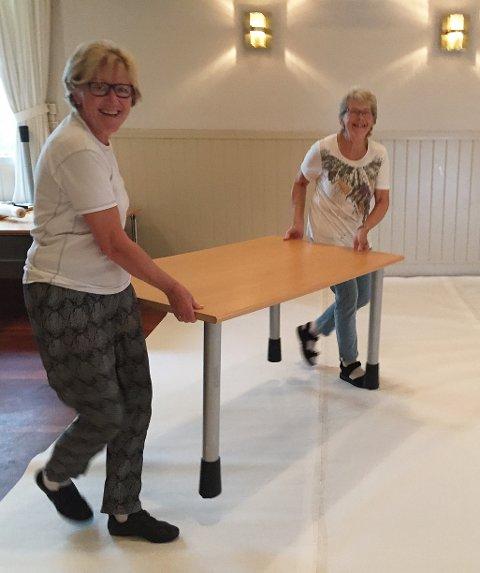 Bære bord: Grethe Gonella (t.v.) og Marit Karlsen sjauer bord i hovedsalen. Gulvene dekkes med maskinpapir for å skåne lakken.
