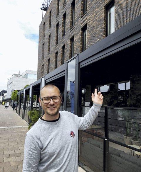 BYGG VED ELVA: Arkitekt Kennet Hald på Elvepromenaden ved et av de bygg i sentrum som han har tegnet, Storgt. 5. FOTO: GLØV