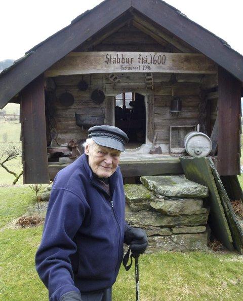 HAUGALANDETS ELDSTE: Rognald Stuhaug framfor Haugalandets eldste trehus – eit stabbur frå 1600 som sto i Vikedal. Legg merke til den nedslitte dørterskelen. Den er nedslitt av mange hogg og stikk i slaktet, fortel 80 års jubilanten. FOTO: SIGMUND HANSEN
