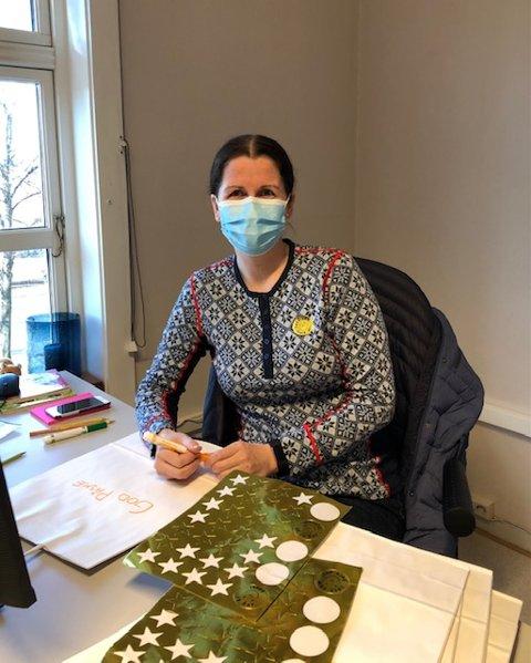 HILSEN: Familiekontakt Lise Solli Hansen skriver påskehilsen på posene gavene skal pakkes i.