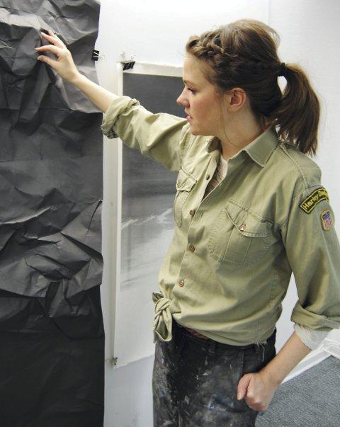 Solgløtt: På et av veggene henger et stort sort arbeide som er påbegynt, som med engang gir assosiasjoner til hennes tidligere arbeid «Solgløtt V».